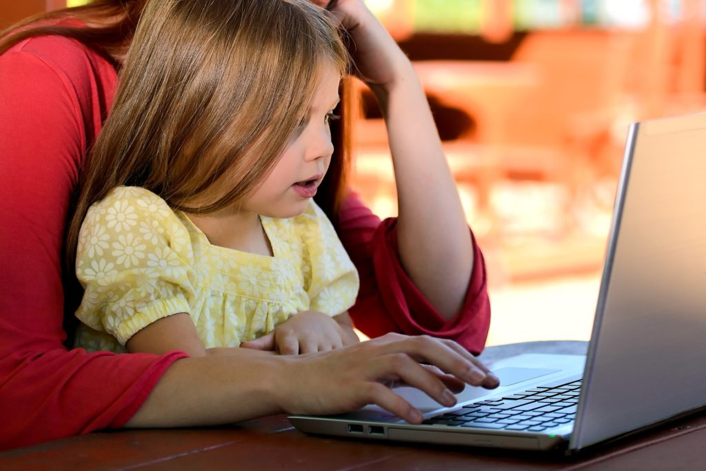 image of little girl and her mother working at a laptop for blog on surviving school summer holidays for working parents