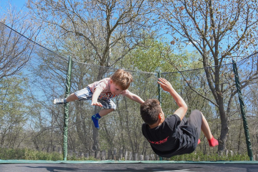 image of two boys jumpin gon a trampoling for blog by Wellspace on surviving the summer holidays for working parents